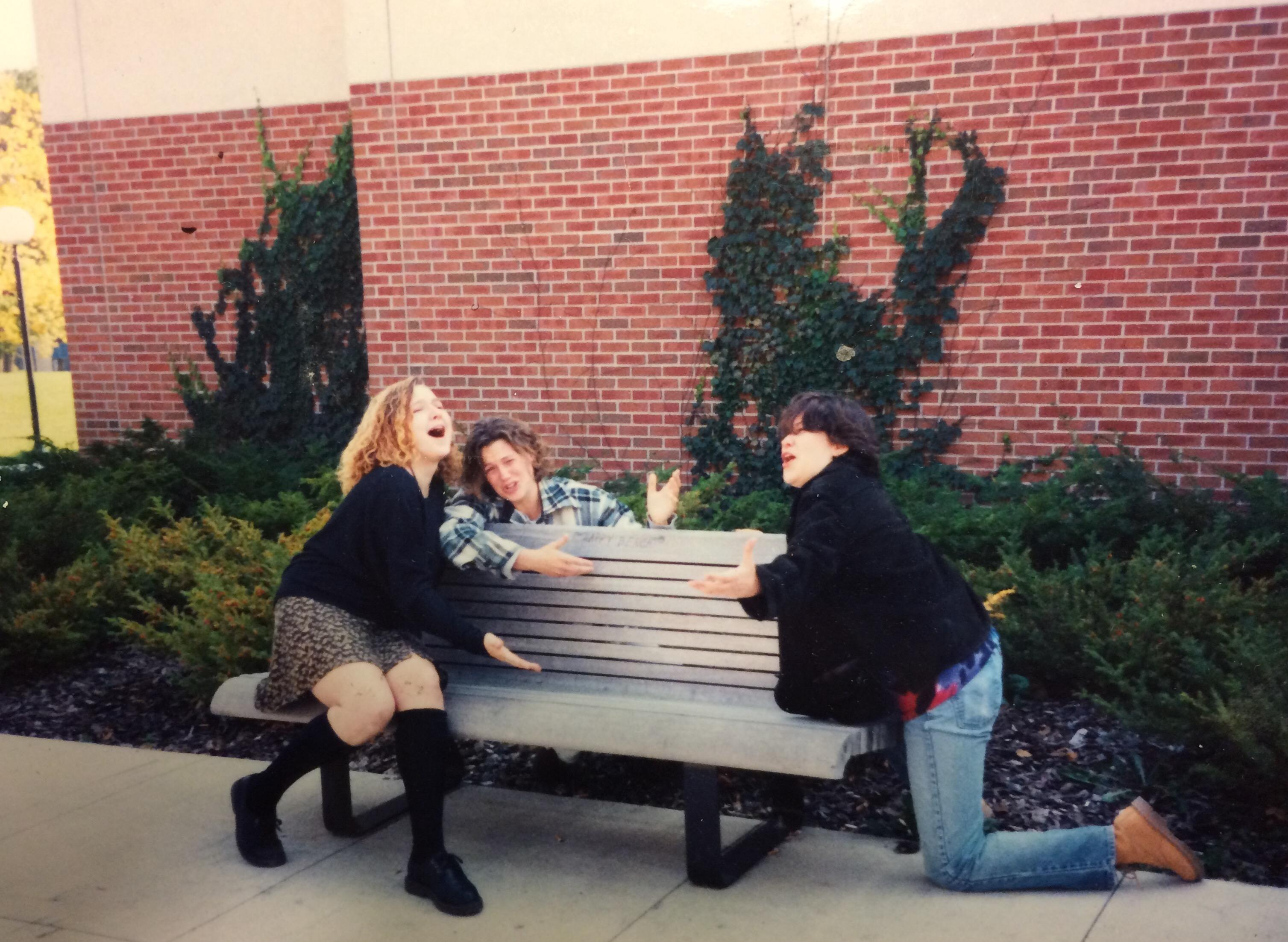Three young women singing on a bench