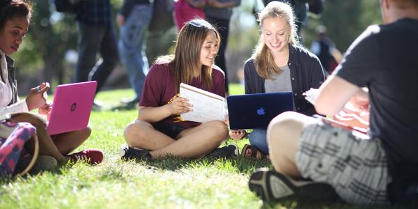 Two female students sitting on a busy outdoor mall