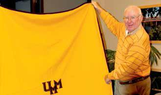 A man holding up a maroon and gold blanket
